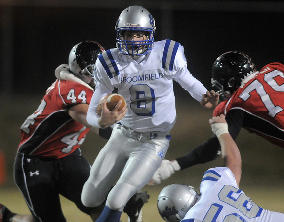 Broomfield's quarterback Aric Kaiser keeps the ball eluding the atckle attempts by Loveland's Conor Mednery and C.J. Walker during Friday's game at Ray Patterson Stadium in Loveland.<br /> November 19, 2010<br /> staff photo/David R. Jennings