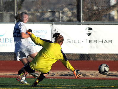 Broomfield's Katie Forsee kicks the ball past Mountain View's goalie Shilee Calhoun to set up a goal during Friday's game at Elizabeth Kennedy Stadium. March 23, 2012  staff photo/ David R. Jennings