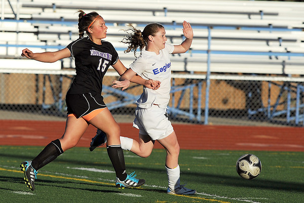 Broomfield's Kristin Snyder moves the ball downfield past Mountain View's Tessa Armstrong during Friday's game at Elizabeth Kennedy Stadium.<br /> March 23, 2012 <br /> staff photo/ David R. Jennings