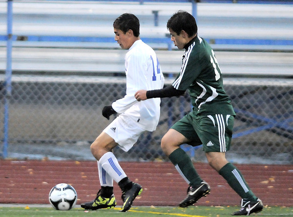 Broomfield's Ricardo Ocampo move the ball past Summit's Max Ortiz during the first round of the state 4A playoffs at Elizabeth Kennedy Stadium on Tuesday.<br /> October 25, 2011<br /> staff photo/ David R. Jennings