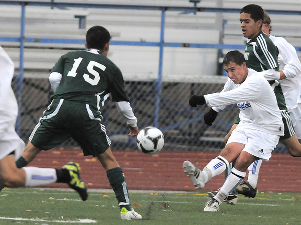 Broomfield's Nick Saunders kicks  the ball past Summit's Alex Roque during the first round of the state 4A playoffs at Elizabeth Kennedy Stadium on Tuesday.<br /> October 25, 2011<br /> staff photo/ David R. Jennings