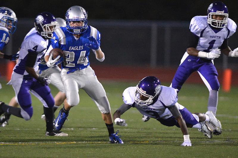 Broomfield's Riley Derus runs the ball downfield avoiding a tackle by  Denver South's Kerrian Chambers during Friday's game at Elizabeth Kennedy Stadium.<br /> September 28, 2012<br /> staff photo/ David R. Jennings