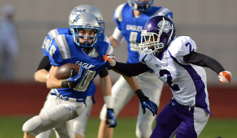 Broomfield's Dylan Plane runs downfield trying to avoid a tackle by Denver South's Cameron French during Friday's game at Elizabeth Kennedy Stadium.<br /> September 28, 2012<br /> staff photo/ David R. Jennings