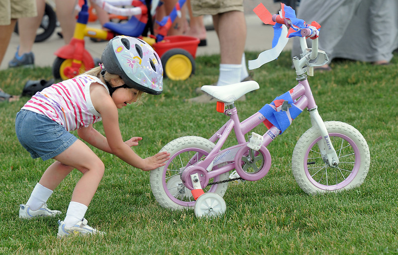 Cassidy Reiser, 4, pushes her bicycle up a hill to get to the line for the bike parade the Great American Picnic at the Broomfield County Commons Park on Monday.<br /> <br /> July 4, 2011<br /> staff photo/ David R. Jennings