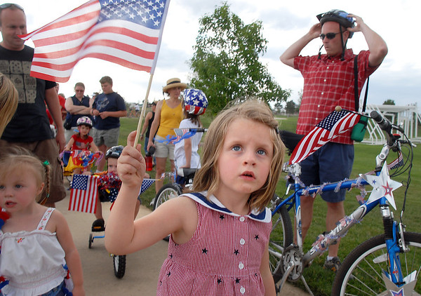 Lauren Micheletti, 4, waves her falg before the bike parade at the Great American Picnic at the Broomfield County Commons Park on Monday.<br /> <br /> July 4, 2011<br /> staff photo/ David R. Jennings