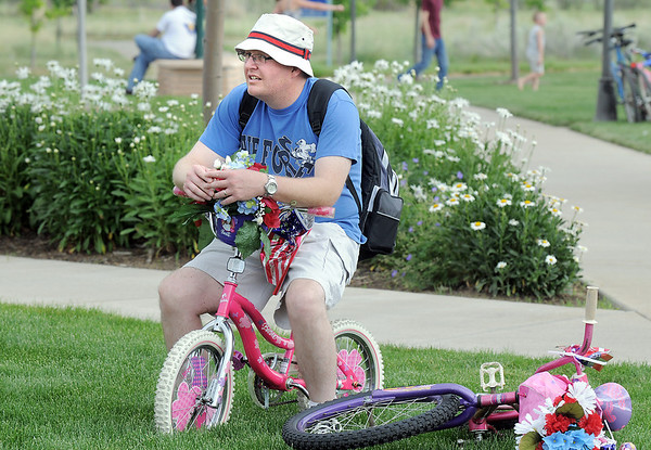 Randy Hinman sits on his daughter's bicycle during the Great American Picnic at the Broomfield County Commons Park on Monday.<br /> <br /> July 4, 2011<br /> staff photo/ David R. Jennings
