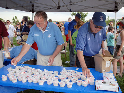 City Council member Dennis McClosky, left, and Mayor Pat Quinn set out ice cream for people during the Great American Picnic at the Broomfield County Commons Park on Monday.  July 4, 2011 staff photo/ David R. Jennings
