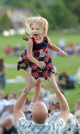 Vivian Sevier, 3, is tossed in the air by her father Blake during the Great American Picnic at the Broomfield County Commons Park on Monday.<br /> <br /> July 4, 2011<br /> staff photo/ David R. Jennings
