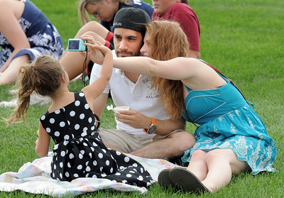 Ingrid Lozada, 3, left, helps her parents Sofia and Gustavo pake a picture of themselves during the Great American Picnic at the Broomfield County Commons Park on Monday.  July 4, 2011 staff photo/ David R. Jennings