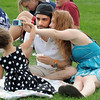 Ingrid Lozada, 3, left, helps her parents Sofia and Gustavo pake a picture of themselves during the Great American Picnic at the Broomfield County Commons Park on Monday.<br /> <br /> July 4, 2011<br /> staff photo/ David R. Jennings