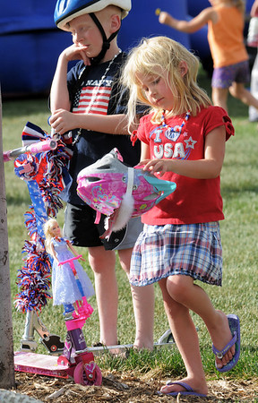 Emily Woods, 5, takes off her helmet after riding in the bike parade with her Barbie and her brother Patrick, 8, during the Great American Picnic at the Broomfield County Commons Park on Monday.<br /> <br /> July 4, 2011<br /> staff photo/ David R. Jennings