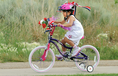 Isabella Martinez, 7, rides her bicycle during the bike parade at the Great American Picnic at the Broomfield County Commons Park on Monday.  July 4, 2011 staff photo/ David R. Jennings