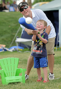 Rhet Behler helps his son Sam, 3, hit a waffle ball while playing a baseball game at the Great American Picnic at the Broomfield County Commons Park on Monday. Home plate is the chair.  July 4, 2011 staff photo/ David R. Jennings