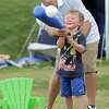 Rhet Behler helps his son Sam, 3, hit a waffle ball while playing a baseball game at the Great American Picnic at the Broomfield County Commons Park on Monday. Home plate is the chair.<br /> <br /> July 4, 2011<br /> staff photo/ David R. Jennings