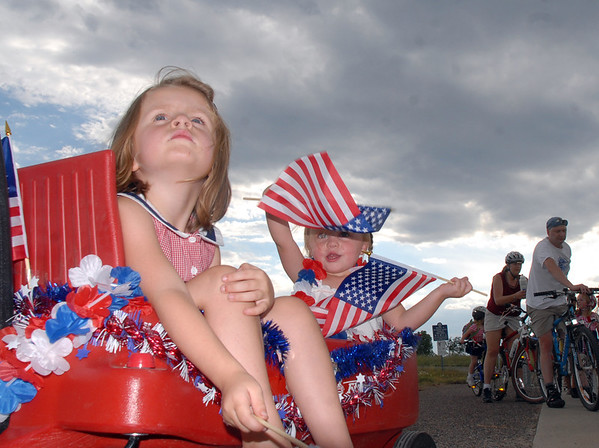 Lauren Micheletti, 4, left, and her sister Emily, 2, wait in their wagon for the bike parade during the Great American Picnic at the Broomfield County Commons Park on Monday.<br /> <br /> July 4, 2011<br /> staff photo/ David R. Jennings