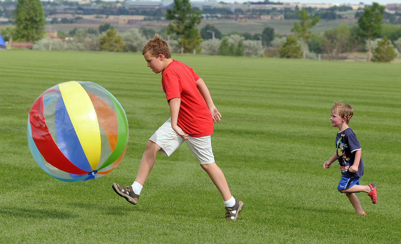 Cade Behler, 9, kicks a big ball while his cousin Sam Behler, 3, runs after him during the Great American Picnic at the Broomfield County Commons Park on Monday.<br /> <br /> July 4, 2011<br /> staff photo/ David R. Jennings