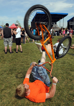 Ian Crockett, 17, plays with his bicycle while laying on the ground during Thursday's Broomstock 2010 at the Broomfield County Commons. <br /> May 27, 2010<br /> Staff photo/ David R. Jennings