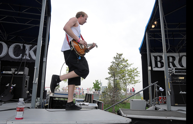 Taylor Kaufman guitarist for 'No Less Than Victory' walks between  stages  while playing during Broomstock at the Broomfield County Commons Park on Thursday.<br /> May 26, 2011<br /> staff photo/David R. Jennings