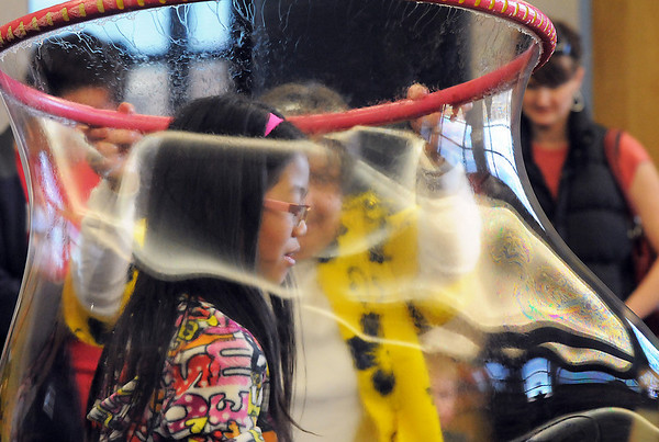 Alisha Heater, 10, is engulfed in a large bubble during the Fun in a Bubble program exploring the world of bubbles at Mamie Doud Eisenhower Public Library on Wednesday. <br /> December 29, 2010<br /> staff photo/David R. Jennings