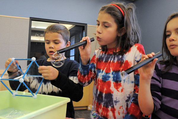 Leo Mowery-Evans, 6, left, with his sister Maya Mowery-Evans, 8, and Lauren Pacheco, 8, make bubbles with various items during the Fun in a Bubble program exploring the world of bubbles at Mamie Doud Eisenhower Public Library on Wednesday. <br /> December 29, 2010<br /> staff photo/David R. Jennings