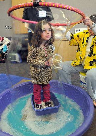 Michelle Rudland, 4, stands inside a large bubble made by Nancy Winkler during the Fun in a Bubble program exploring the world of bubbles at Mamie Doud Eisenhower Public Library on Wednesday. <br /> December 29, 2010<br /> staff photo/David R. Jennings