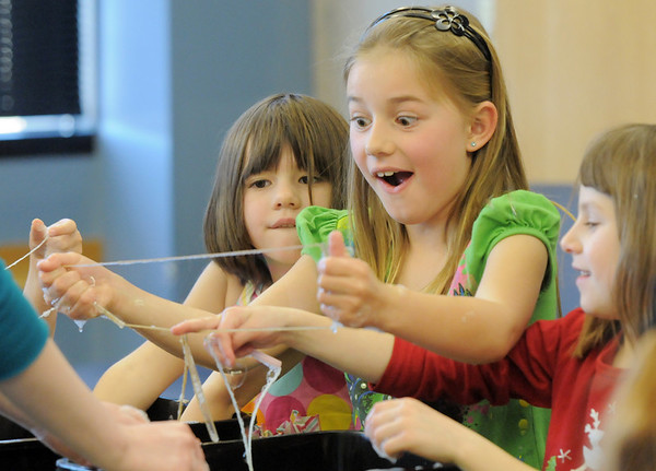 Ava Barjenbruch, 7, crosses strings with Josie Pepperdine, 7, right, while making bubbles during the Fun in a Bubble program exploring the world of bubbles at Mamie Doud Eisenhower Public Library on Wednesday. <br /> December 29, 2010<br /> staff photo/David R. Jennings