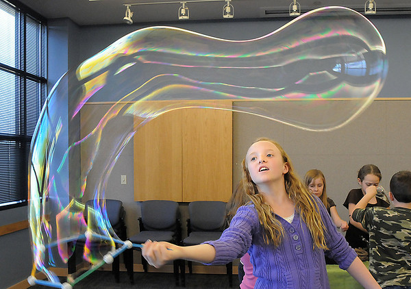 Ashlyn Elggren, 10, waves a wand to make a large bubble during the Fun in a Bubble program exploring the world of bubbles at Mamie Doud Eisenhower Public Library on Wednesday. <br /> December 29, 2010<br /> staff photo/David R. Jennings