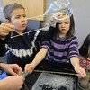 Leo Mowery-Evans, 6, left, Lauren Pacheco, 8, and her sister Elena Pacheco, 4, work on making bubbles with strings during the Fun in a Bubble program exploring the world of bubbles at Mamie Doud Eisenhower Public Library on Wednesday. <br /> December 29, 2010<br /> staff photo/David R. Jennings