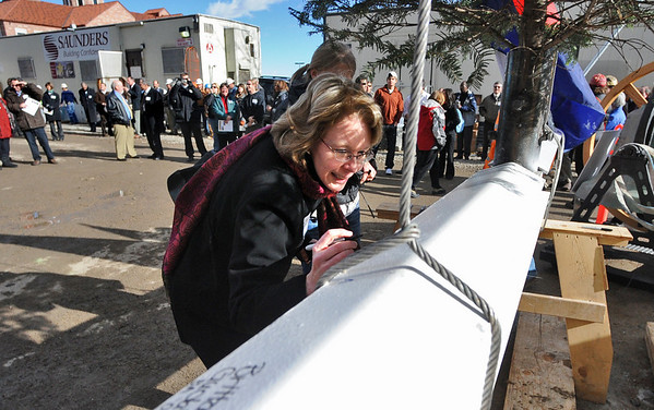 "TOPPING01<br /> Jeanie Bell, who works in admissions, signs the final beam during a ""topping-off ceremony"" at the University of Colorado's Center for Community building on Monday. <br /> <br /> Photo by Marty Caivano/Camera/Dec. 14, 2009"