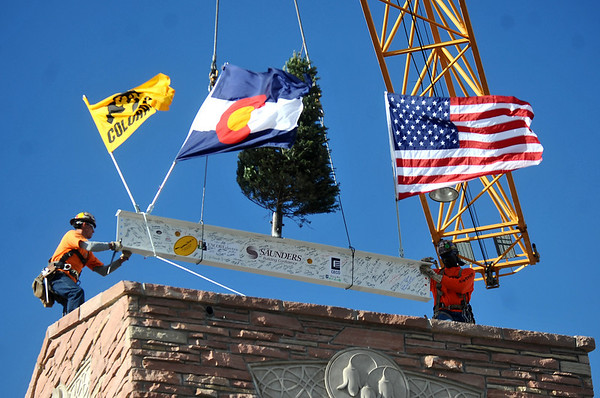 "TOPPING04<br /> Workers move the final beam into place during a ""topping-off ceremony""<br /> at the University of Colorado's Center for Community building on Monday. <br /> <br /> Photo by Marty Caivano/Camera/Dec. 14, 2009"