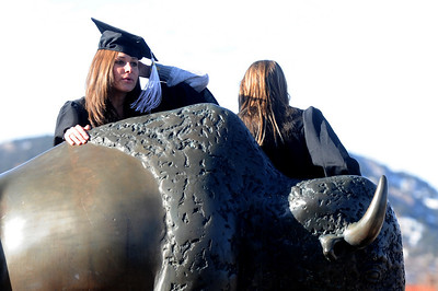 GRAD22 Jill Hulley, left, and Ashley VenHorst cling to the buffalo statue outside the Coors Event Center while getting their pictures taken  after the University of Colorado's winter commencement on Friday.  Photo by Marty Caivano/Camera/Dec. 18, 2009
