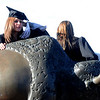 GRAD22<br /> Jill Hulley, left, and Ashley VenHorst cling to the buffalo statue outside the Coors Event Center while getting their pictures taken  after the University of Colorado's winter commencement on Friday.<br /> <br /> Photo by Marty Caivano/Camera/Dec. 18, 2009