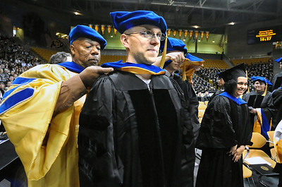 GRAD14 Alexander Zolot, right, is hooded by marshall and assistant vice chancellor Alphonse Keasley during the University of Colorado's winter commencement on Friday. Zolot received a Ph.D in chemical physics.  Photo by Marty Caivano/Camera/Dec. 18, 2009