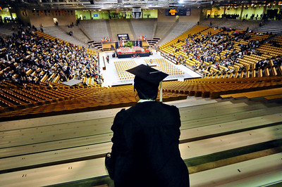 GRAD03 A graduate watches the Coors Event Center fill up with friends and family before the University of Colorado's winter commencement on Friday.  Photo by Marty Caivano/Camera/Dec. 18, 2009