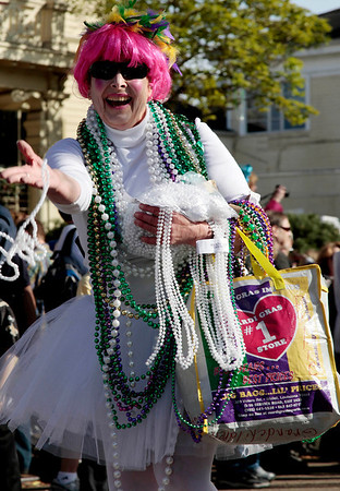 "Mardi Gras.JPEG-0b063.JPG A member of a marching group tosses beads as she walks through the streets in the Mardi Gras ""Krewe of Tucks"" parade drives through the streets of New Orleans, Monday, Feb. 20, 2012. It may be just another Monday anywhere else, but in New Orleans it's Lundi Gras the day before the Carnival season culminates on Fat Tuesday.  (AP Photo/Bill Haber)"
