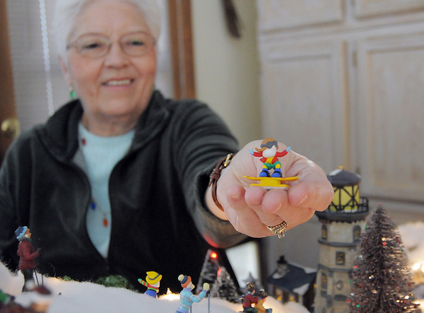 Carol Clever shows a snowboarding elf for her Christmas Village containing 53 buildings and over 2000 accessories on a 14 foot long and four foot wide table at their home on Saturday.<br /> December 17, 2011<br /> Staff photo/ David R. Jennings