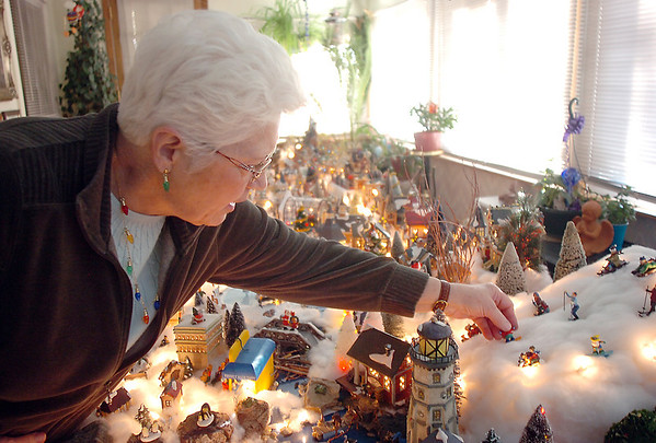 Carol Clever adjusts a snowboarding elf in her Christmas village containing 53 buildings and over 2000 accessories on a 14 foot long and four foot wide table at their home on Saturday.<br /> December 17, 2011<br /> Staff photo/ David R. Jennings
