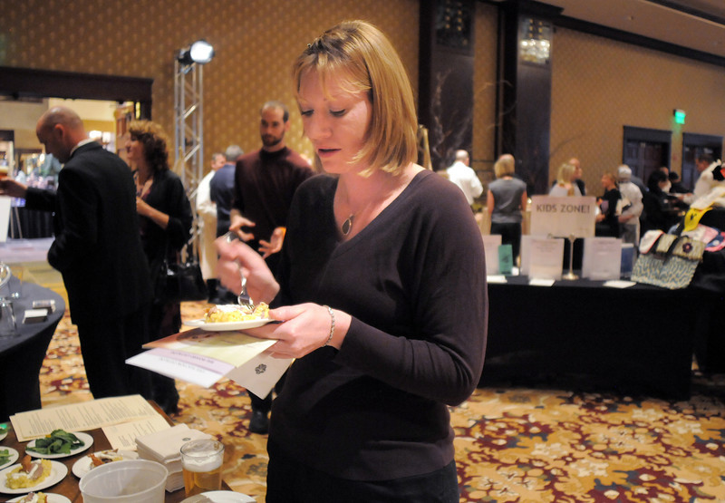 Amanda Crowe samples food prepared by executive chef Timothy Payne of Terroir Restaurant at the March of Dimes Signature Chefs Auction at the Omni Interlocken Resort on Thursday.<br /> <br /> October 21, 2010<br /> staff photo/David R. Jennings