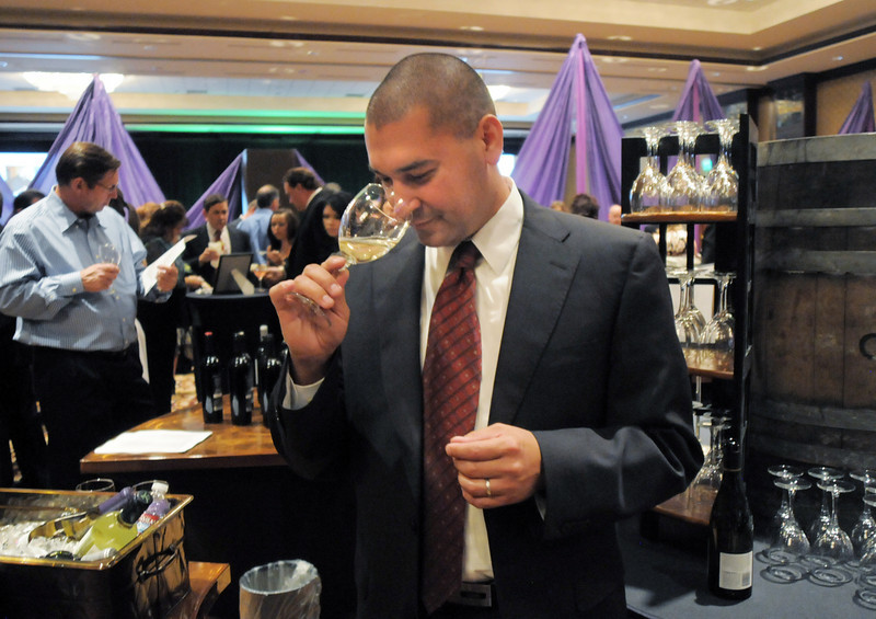 Ben Chavez with Southern Wine & Spirits of Colorado, sniffs a glass of wine at the March of Dimes Signature Chefs Auction at the Omni Interlocken Resort on Thursday.<br /> <br /> October 21, 2010<br /> staff photo/David R. Jennings