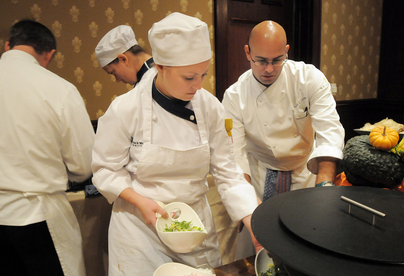 Chef Daniel Cofrades, right, of Jill's Restaurant at the St. Julien supervises Erica Began a Johnson and Wales student while perparing dishes at the March of Dimes Signature Chefs Auction at the Omni Interlocken Resort on Thursday.<br /> <br /> October 21, 2010<br /> staff photo/David R. Jennings