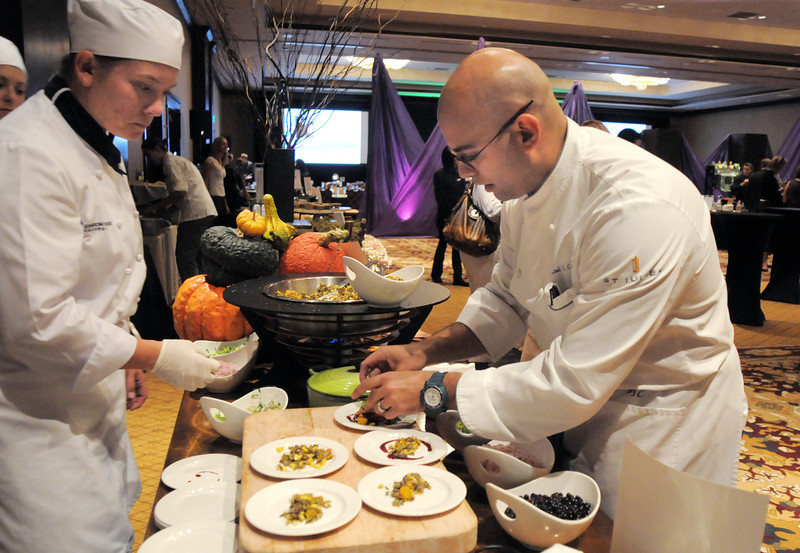Jenica Flippo, left, Johnson and Wales University student, helps prepare food with Jill's Restaurant chef de cuisine Daniel Cofrades at the March of Dimes Signature Chefs Auction at the Omni Interlocken Resort on Thursday.<br /> <br /> October 21, 2010<br /> staff photo/David R. Jennings