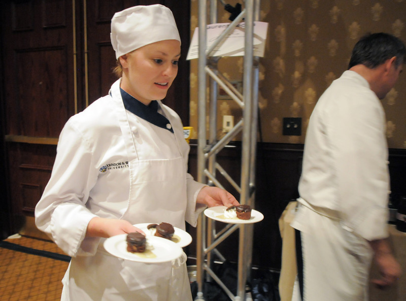 Erica Began, a Johnson and Wales University student, assists executive chef Laurent Mechin of Jill's Restaurant at the March of Dimes Signature Chefs Auction at the Omni Interlocken Resort on Thursday.<br /> <br /> October 21, 2010<br /> staff photo/David R. Jennings