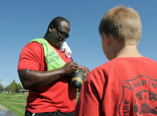 Darius Holland autographs a football for Paxton VanWanseele, 12, during  Saturday's 2011 Children's Wellness Adventure at Community Park.<br /> August 27, 2011<br /> staff photo/ David R. Jennings