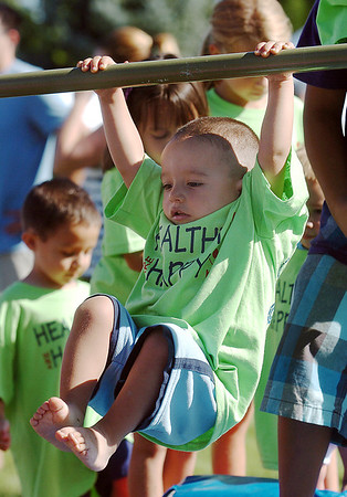 Nicholas Jezierski, 2, swings on a bar while going through an obstacle course during  Saturday's 2011 Children's Wellness Adventure at Community Park.<br /> <br /> August 26, 2011<br /> staff photo/ David R. Jennings