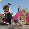 Tyler Dunn, 4, left, and Bella Schnepp, 5, work on their chalk art during  Saturday's 2011 Children's Wellness Adventure at Community Park.<br /> August 27, 2011<br /> staff photo/ David R. Jennings