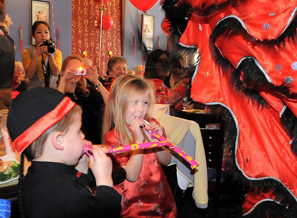 Cole Bialek, 4, left, and his cousin Ava Noregren, 5, celebrate with a Lion during the traditional Lion Dance for Chinese new year at United Chinese Restaurant in Broomfield on Sunday. February 3rd is the beginning of the Chinese New Year, the year of the rabbit.<br /> <br /> January 30, 2011<br /> staff photo/David R. Jennings