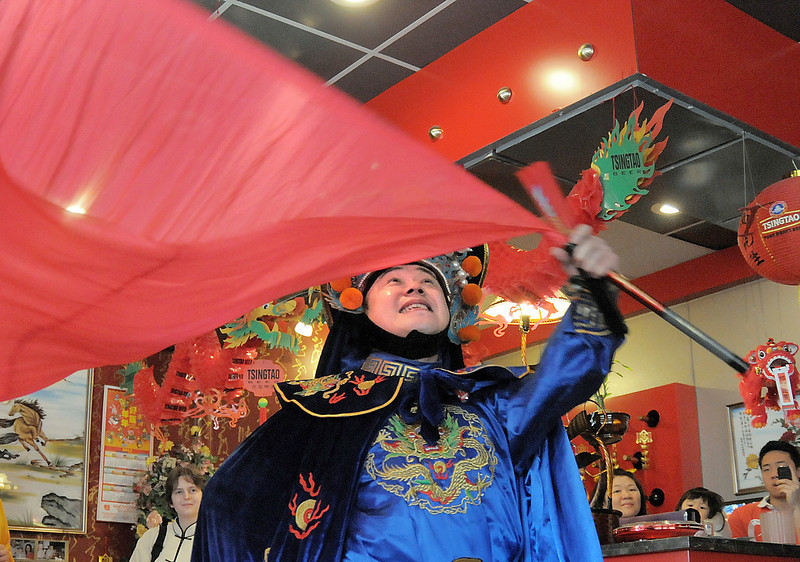 Magician Peng Li, from New York,  a master of the Chinese art of face mask changing, BianLian, waves a flag after revealing his face while performing for the Chinese new year celebration at United Chinese Restaurant on Sunday. February 3rd is the beginning of the Chinese New Year, the year of the rabbit.<br /> <br /> January 30, 2011<br /> staff photo/David R. Jennings