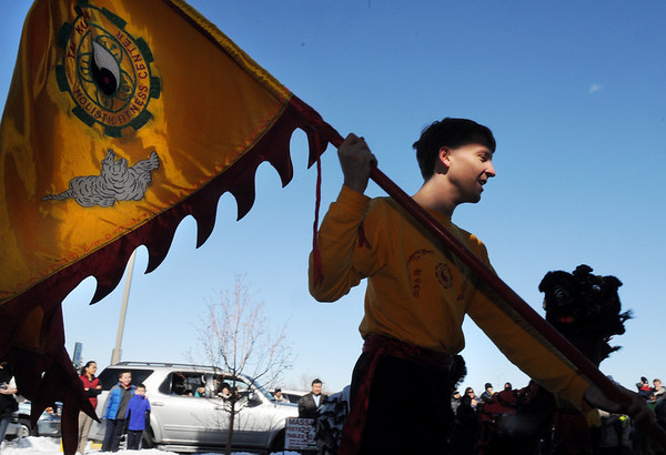Daniel Mieritz with the Tai Kung Ha Holistic Fitness Center carries a flag during the performance of the Lion Dance for Chinese New Year, the year of the Tiger, at Pacific Ocean Marketplace in Broomfield on Sunday.<br /> <br /> February 14, 2010<br /> Staff photo/David R. Jennings