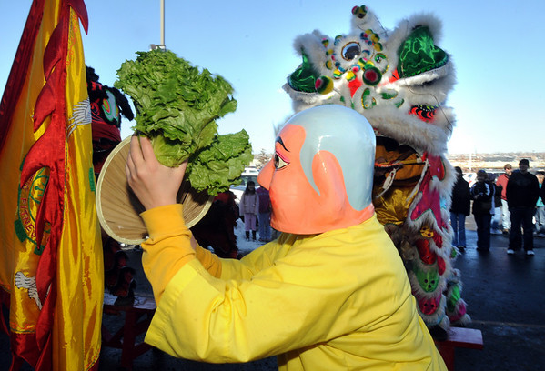 The Happy Buddha, Alexandra Ralat, holds the lettuce for the three Lions for their dance at the Pacific Ocean Marketplace in Broomfield on Sunday. The members of the Tai Kung Ha Holistic Fitness Center perform the Lion Dance to help bring in the Chinese New Year, the year of the Tiger.<br /> <br /> February 14, 2010<br /> Staff photo/David R. Jennings
