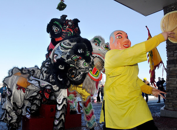 The Happy Buddha, Alexandra Ralat, guides the lions with Tai Kung Ha Holistic Fitness Center in to the Pacific Ocean Marketplace during the Lion Dance in celebration of the Chinese New Year, the year of the Tiger, on Sunday.<br /> <br /> <br /> February 14, 2010<br /> Staff photo/David R. Jennings